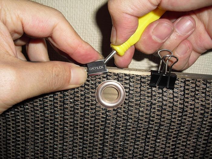 ガチャ玉と網戸枠の間にマイナスドライバーで隙間を作りシェードを挟み込んでいる写真